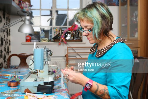 Seamstress cutting fabric working at home. : Foto de stock