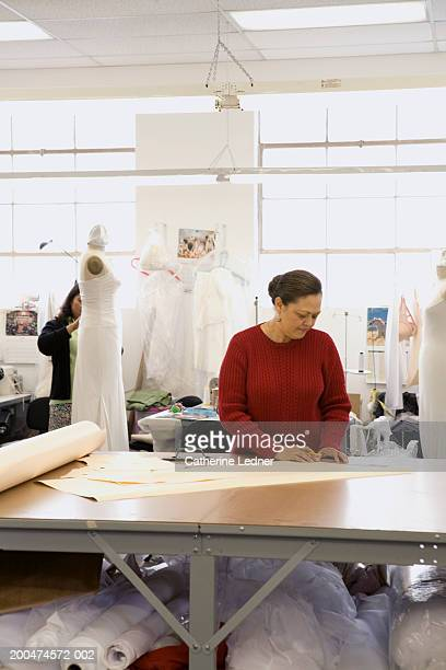 Seamstress cutting out wedding patterns in factory