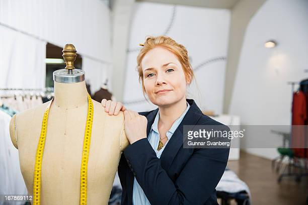 Seamstress leaning against a mannequin.