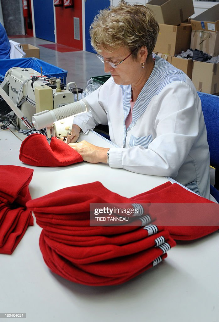 A seamstress makes red bonnets October 31, 2013 at the textile factory Armor Lux in Quimper, western France. These red bonnets became a symbol of anger in Brittany's social crisis.