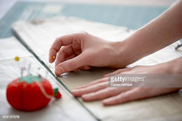 Seamstress pinning pattern to fabric