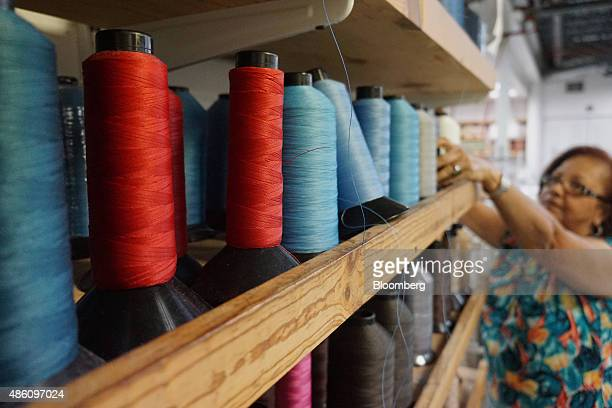 A seamstress pulls thread from a spool at the Pavilion Furniture Inc manufacturing facility in Miami Florida US on Friday Aug 28 2015 The Institute...