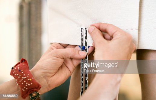 Seamstress puts pins in dress hem