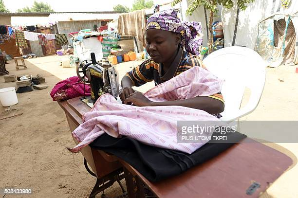 A seamstress sews clothes for Internally Displaced Persons in Maiduguri northeast Nigeria on February 4 2016 The Nigerian city of Maiduguri has been...