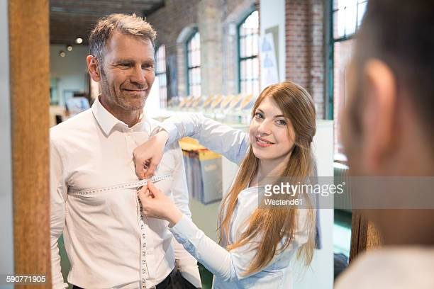 Seamstress taking chest measurement of client