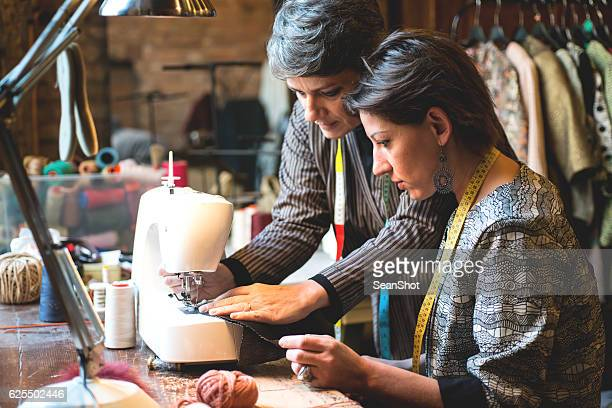 Seamstress Teaching her Assistant how to Use the Sewing Machine