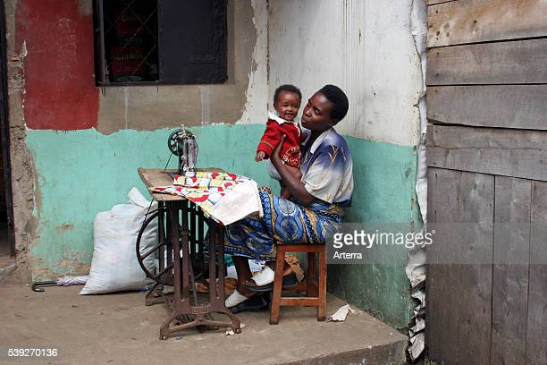 Seamstress with child working with old Usha treadle sewing machine at home Ruhengeri Musanze Rwanda Central Africa