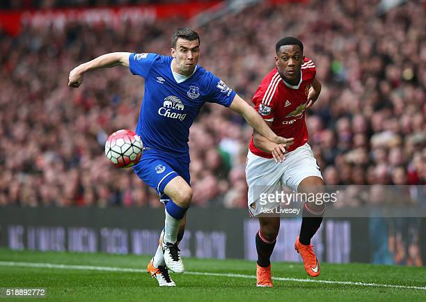 Seamus Coleman of Everton and Anthony Martial of Manchester United chase the ball during the Barclays Premier League match between Manchester United...