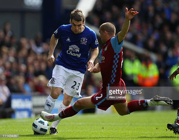 Seamus Coleman of Everton is tackled by Luke Young of Aston Villa during the Barclays Premier League match between Everton and Aston Villa at...