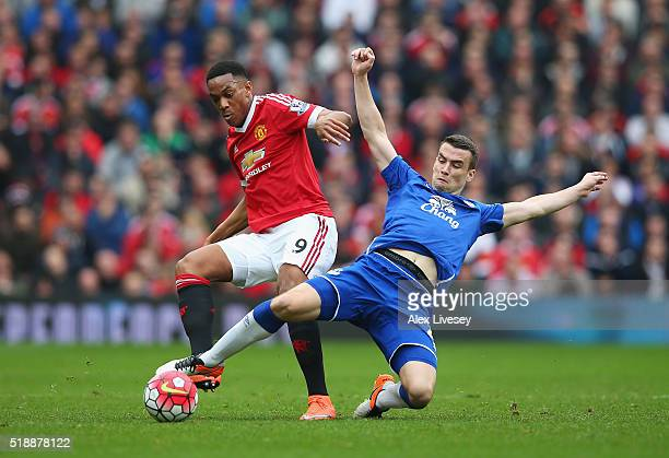 Seamus Coleman of Everton stretches to tackle Anthony Martial of Manchester United during the Barclays Premier League match between Manchester United...