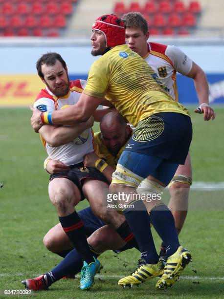 Sean Armstrong of Germany is challenged by Johan van Heerden and Mihai Lazar of Romania during the European Shield Rugby match between Germany and...