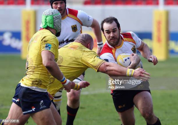 Sean Armstrong of Germany is challenged by Mihai Lazar and Florin Surugiu of Romania during the European Shield Rugby match between Germany and...