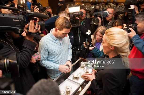 Sean Azzariti a veteran of the Iraq war prepares to make the first legal recreational marijuana purchase in Colorado from advocate Betty Aldworth at...