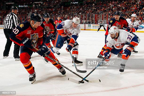 Sean Bergenheim of the Florida Panthers crosses sticks with Brian Strait and Casey Cizikas of the New York Islanders at the BBT Center on January 14...