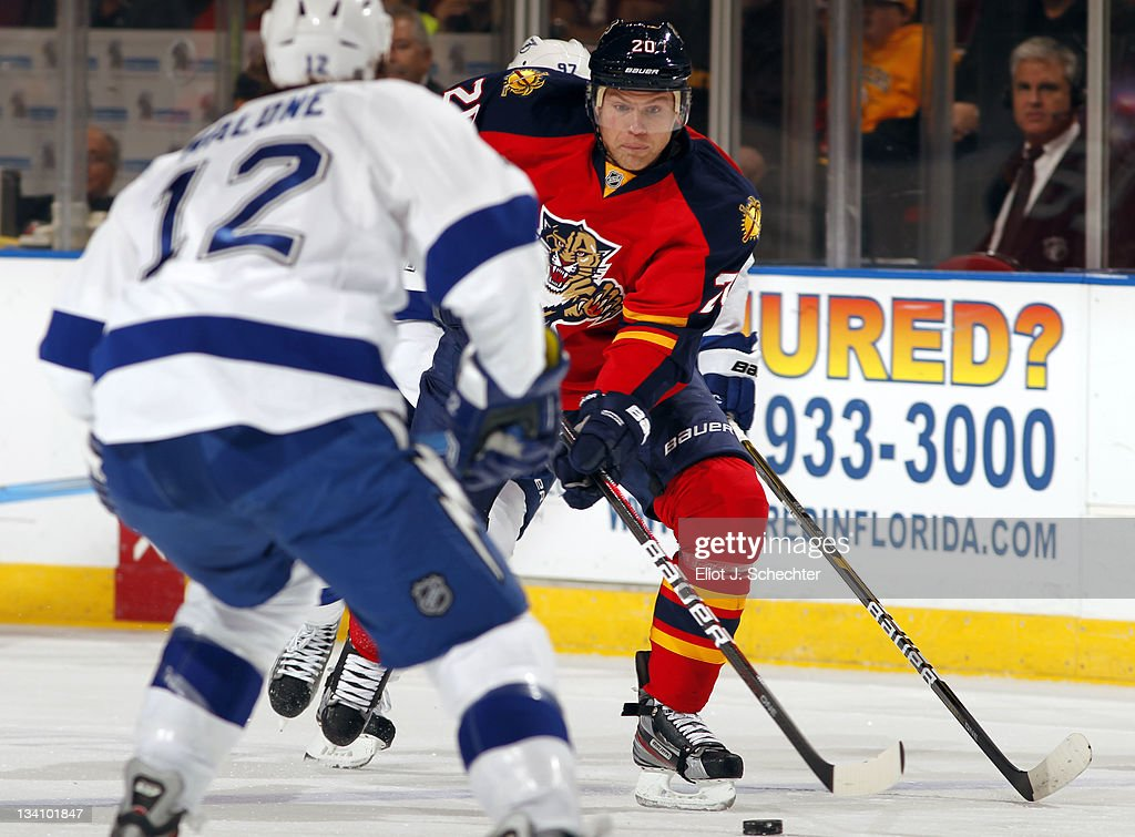 Sean Bergenheim of the Florida Panthers skates with the puck against Ryan Malone of the Tampa Bay Lightning at the BankAtlantic Center on November 25...