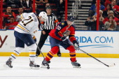 Sean Bergenheim of the Florida Panthers skates with the puck against Drew Stafford of the Buffalo Sabres at the BBT Center on March 7 2014 in Sunrise...