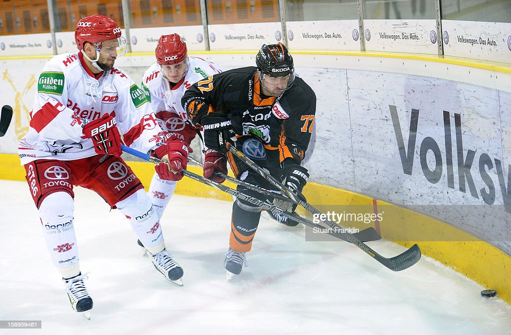 Sean Blanchard of Wolfsburg challenges for the puck with <a gi-track='captionPersonalityLinkClicked' href=/galleries/search?phrase=Felix+Schuetz&family=editorial&specificpeople=670468 ng-click='$event.stopPropagation()'>Felix Schuetz</a> of Cologne during the DEL match between Grizzly Adams Wolfsburg and Kolner Haie at the Volksbank BraWo Eisarena on January 4, 2013 in Wolfsburg, Germany