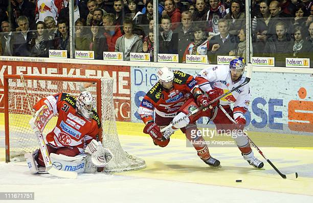 Sean Brown of KAC and Thomas Raffl of Salzburg fight for the puck next to goalkeeper Andy Chiodo of KAC during the EHL match between EC KAC and Red...