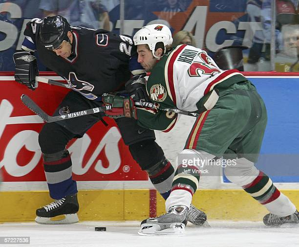 Sean Brown of the Vancouver Canucks and Alex Henry of the Minnesota Wild battle for the puck at General Motors Place on March 31 2006 in Vancouver...