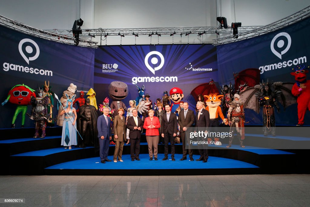 Sean Casey, Henriette Reker, Armin Laschet, Felix Falk, Tobias Haar and Gerald Boese welcome German Chancellor Angela Merkel (C) at the Gamescom 2017 gaming trade fair during the media day on August 22, 2017 in Cologne, Germany. Gamescom is the world's largest digital gaming trade fair and will be open to the public from August 22-26.
