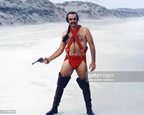 Sean Connery British actor holding a handgun while wearing thighhigh boots and red costume with his hair in a pony tail standing in a snowy landscape...