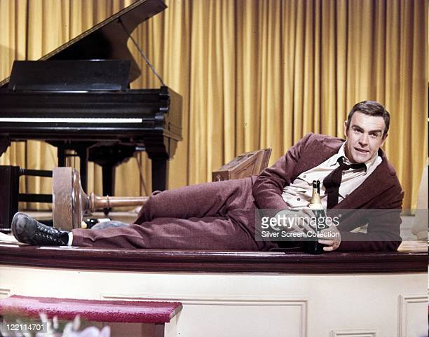 Sean Connery British actor wearing a brown suit reclining on a stage with a bottle of champagne in his hands and a grand piano in the background in a...