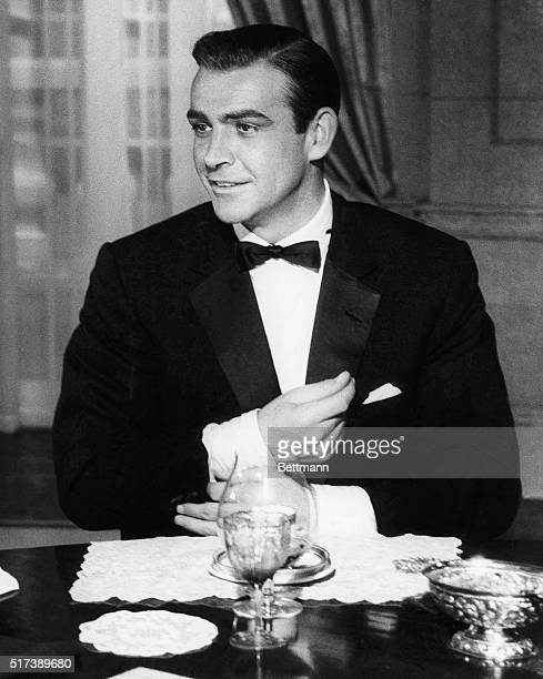 Sean Connery in a scene from Goldfinger adjusts a cuff of his tuxedo while dining with M and the Prime Minister