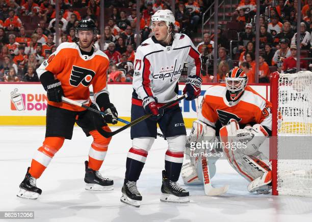 Sean Couturier and Brian Elliott of the Philadelphia Flyers defend TJ Oshie of the Washington Capitals on October 14 2017 at the Wells Fargo Center...