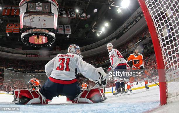Sean Couturier and Ivan Provorov of the Philadelphia Flyers react to the play alongside the net of Philipp Grubauer and Evgeny Kuznetsov of the...