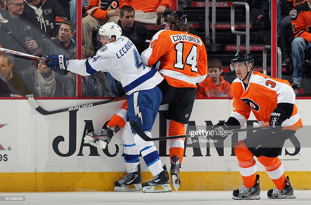 Sean Couturier #14 and Kurtis Foster #3 of the Philadelphia Flyers battle against Vincent LeCavalier #4 of the Tampa Bay Lightning on February 5, 2013 at the Wells Fargo Center in Philadelphia, Pennsylvania.