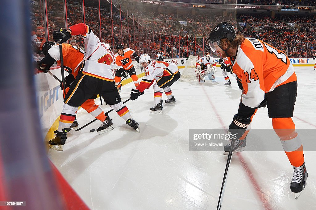 Sean Couturier #14 and Steve Downie #9 of the Philadelphia Flyers wait as teammate Matt Read #24 battles for the puck with Dennis Wideman #6 and Mikael Backlund #11 of the Calgary Flames at the Wells Fargo Center on February 8, 2014 in Philadelphia, Pennsylvania. The Flyers won 2-1.