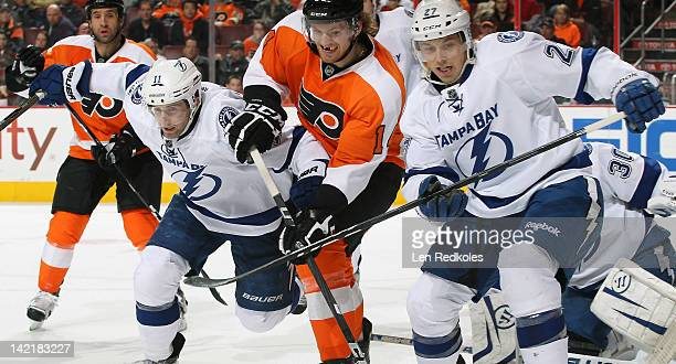 Sean Couturier of the Philadelphia Flyers battles against Tom Pyatt and Bruno Gervais of the Tampa Bay Lightning on March 26 2012 at the Wells Fargo...