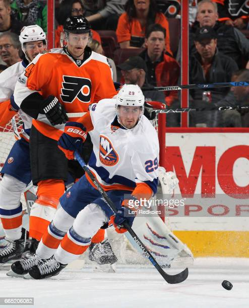 Sean Couturier of the Philadelphia Flyers battles for control of the puck between Brock Nelson and Travis Hamonic of the New York Islanders on March...