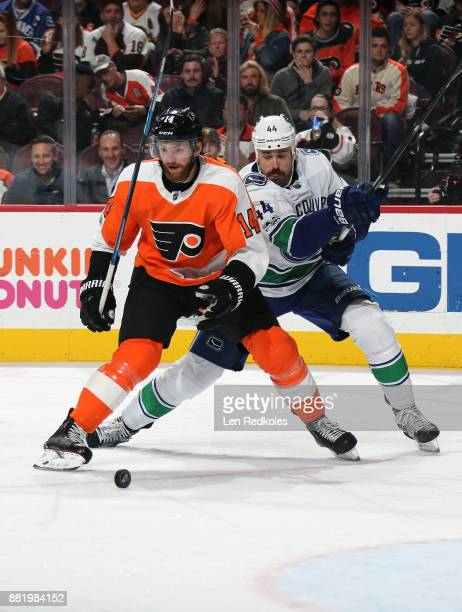Sean Couturier of the Philadelphia Flyers battles for the puck against Erik Gudbranson of the Vancouver Canucks on November 21 2017 at the Wells...