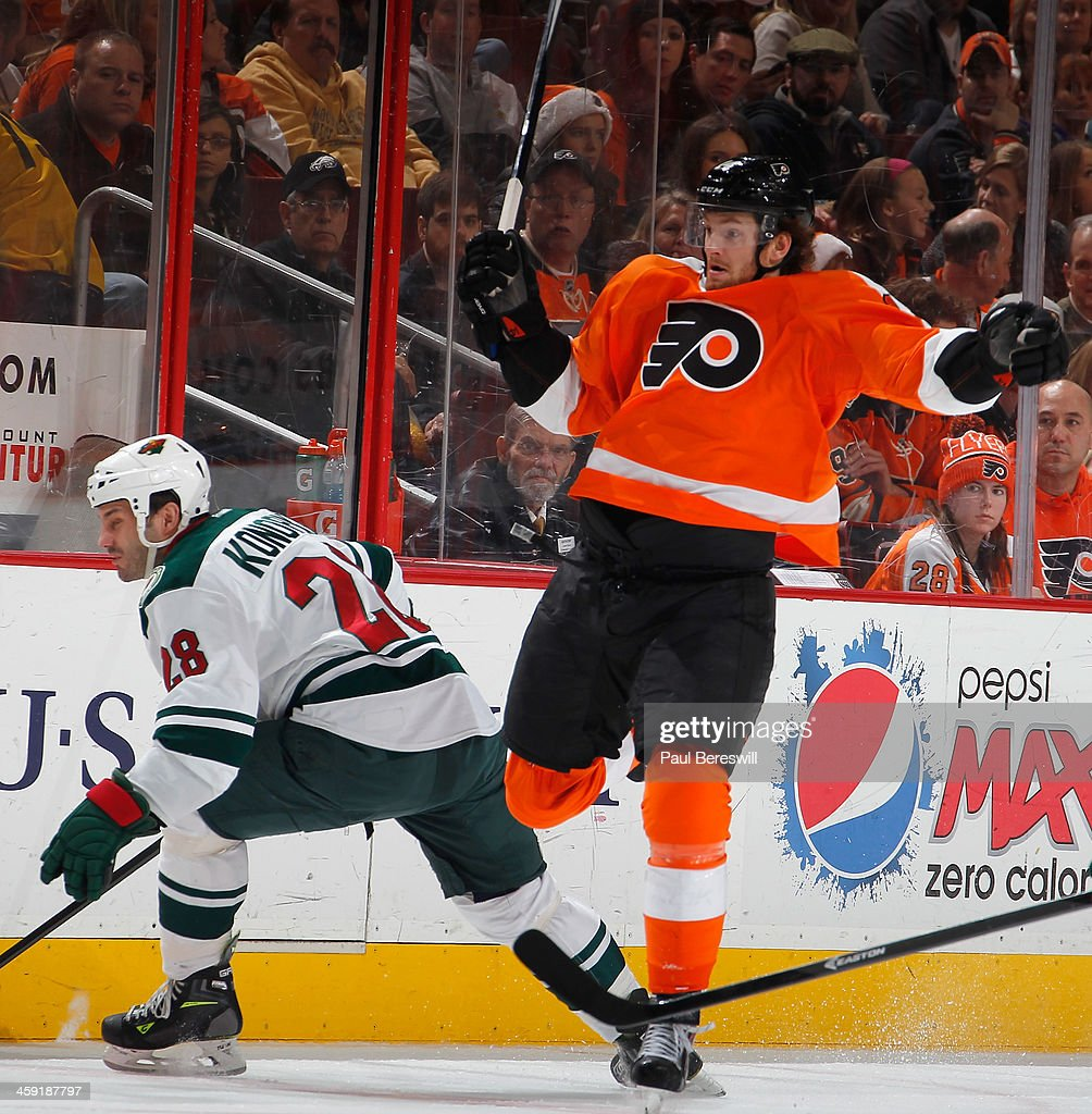 <a gi-track='captionPersonalityLinkClicked' href=/galleries/search?phrase=Sean+Couturier&family=editorial&specificpeople=5663953 ng-click='$event.stopPropagation()'>Sean Couturier</a> #14 of the Philadelphia Flyers leaps away to avoid a hard check by <a gi-track='captionPersonalityLinkClicked' href=/galleries/search?phrase=Zenon+Konopka&family=editorial&specificpeople=2105876 ng-click='$event.stopPropagation()'>Zenon Konopka</a> #28 of the Minnesota Wild during the second period of an NHL hockey game at Wells Fargo Center on December 23, 2013 in Philadelphia, Pennsylvania.