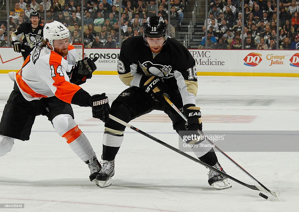 Sean Couturier #14 of the Philadelphia Flyers pokes the puck away from James Neal #18 of the Pittsburgh Penguins on April 12, 2014 at Consol Energy Center in Pittsburgh, Pennsylvania.