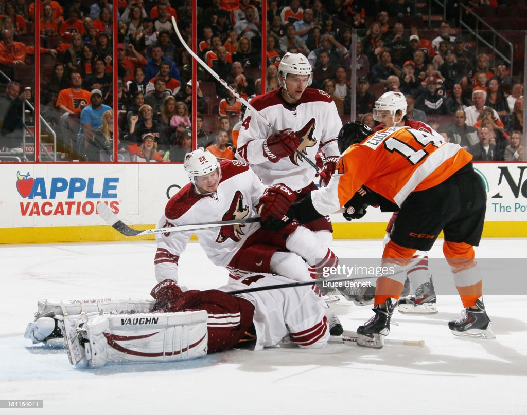 <a gi-track='captionPersonalityLinkClicked' href=/galleries/search?phrase=Sean+Couturier&family=editorial&specificpeople=5663953 ng-click='$event.stopPropagation()'>Sean Couturier</a> #14 of the Philadelphia Flyers pushes <a gi-track='captionPersonalityLinkClicked' href=/galleries/search?phrase=Oliver+Ekman-Larsson&family=editorial&specificpeople=5894618 ng-click='$event.stopPropagation()'>Oliver Ekman-Larsson</a> #23 of the Phoenix Coyotes over hit goaltender <a gi-track='captionPersonalityLinkClicked' href=/galleries/search?phrase=Thomas+Greiss&family=editorial&specificpeople=695275 ng-click='$event.stopPropagation()'>Thomas Greiss</a> #1 during the second period at the Wells Fargo Center on October 11, 2013 in Philadelphia, Pennsylvania.