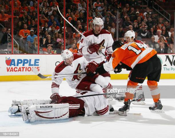 Sean Couturier of the Philadelphia Flyers pushes Oliver EkmanLarsson of the Phoenix Coyotes over hit goaltender Thomas Greiss during the second...