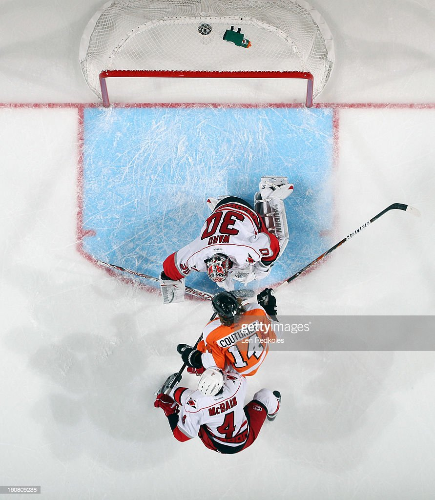 Sean Couturier #14 of the Philadelphia Flyers takes a shot on goal against Cam Ward #30 and Jamie McBain #4 of the Carolina Hurricanes on February 2, 2013 at the Wells Fargo Center in Philadelphia, Pennsylvania.