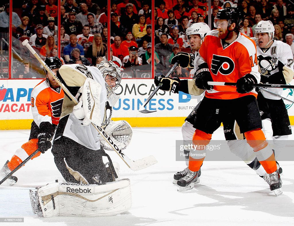 Sean Couturier #14 of the Philadelphia Flyers watches as goalie Marc-Andre Fleury #29 of the Pittsburgh Penguins makes a save in the second period of an NHL hockey game at Wells Fargo Center on March 15, 2014 in Philadelphia, Pennsylvania.