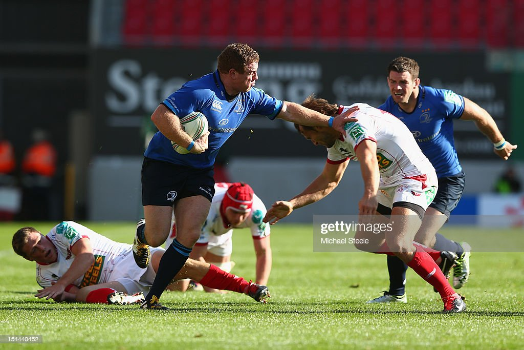 Sean Cronin (C) of Leinster holds off Andy Fenby (R) of Scarlets during the Heineken Cup Pool 5 match between Scarlets and Leinster at Parc y Scarlets on October 20, 2012 in Llanelli, Wales.