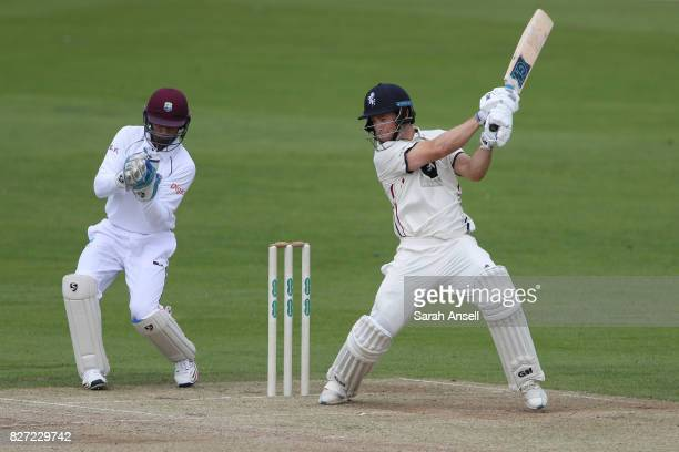 Sean Dickson of Kent hits a boundary as West Indies wicket keeper Shane Dowrich looks on during day two of the tour match between Kent and West...