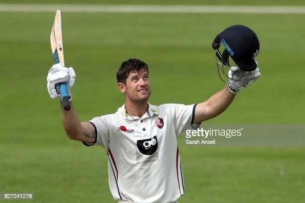 Sean Dickson of Kent raises his bat after reaching a century during day two of the tour match between Kent and West Indies at The Spitfire Ground on...