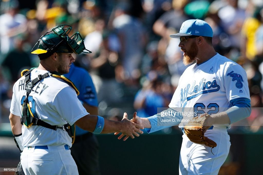 Sean Doolittle #62 of the Oakland Athletics celebrates with Josh Phegley #19 after the game against the New York Yankees at the Oakland Coliseum on June 17, 2017 in Oakland, California. The Oakland Athletics defeated the New York Yankees 5-2. Players and umpires are wearing blue to celebrate Father's Day weekend and support prostrate cancer awareness.