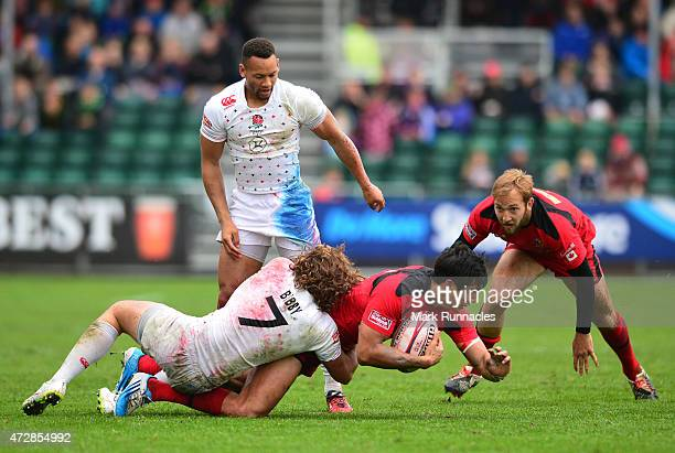 Sean Duke of Canada is tackled by Dann Bibby and Dan Norton of England during the Emirates Airlines Rugby 7s match between Canada and England at...