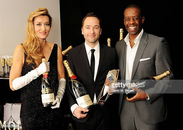 Sean Ellis winner of Best British Independent Film for 'Metro Manila' poses with presenters Natascha McElhone and Adrian Lester backstage at the Moet...