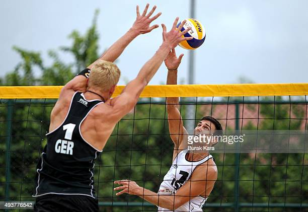Sean Faiga of Israel spikes Tim Holler of Germany is in action during the 3rd day of the FIVB Antalya Open beach volley tournament October 22 in the...