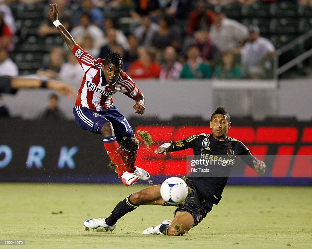 Sean Franklin of Los Angeles Galaxy slide tackles Miller Bolanos of Chivas USA during the MLS match at The Home Depot Center on August 12 2012 in...