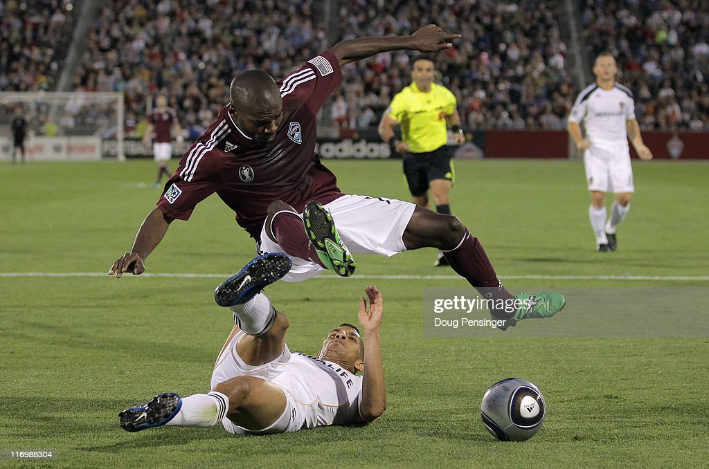 Sean Franklin of the Los Angeles Galaxy kicks the ball away from Omar Cummings of the Colorado Rapids at Dick's Sporting Goods Park on June 18 2011...