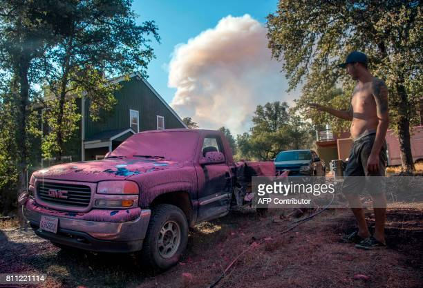 TOPSHOT Sean Greenlaw views his truck covered in fire retardant as a smoke plume billows in the background near Oroville California on July 08 2017...